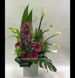 Arrangement floral moderne composé d'une orchidée violette, de gerberas fuchsia, de callas blancs et d'un feuillage exotique.