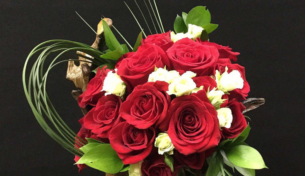 Bouquet de roses rouges et de rosettes blanches.