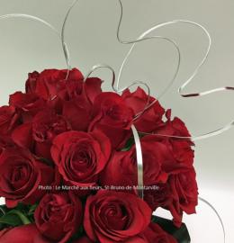 Bouquet de 24 roses rouges assorti de cœurs argentés.