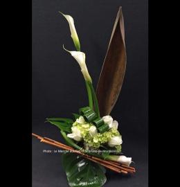 Création funéraire Calixa. Arrangement moderne et zen composé de bois, d'élégants feuillages et de fleurs nobles (callas, roses et hydrangées). De 80$ à 100$.