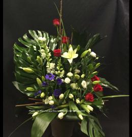 Création funéraire Gaspé. Magnifique jardin d'été garni de roses, mufliers, lys, tulipes et anémones, adossé aux larges feuilles de Monstera. De 150$ à 200$.