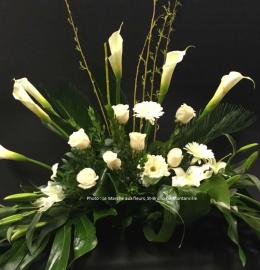 Création funéraire Kamouraska. Composition rayonnante et apaisante de feuillages luxuriants et de fleurs blanches (callas, roses, lys et gerberas). De 120$ à 150$.