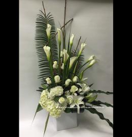 Création funéraire Montréal. Composition majestueuse où s'élèvent des callas et des roses au milieu d'un parterre de lys et d'hydrangées. De 175$ à 220$.