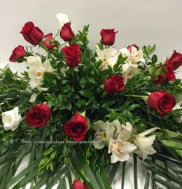 Coussin de cercueil Amour. Coussin garni de roses rouges, callas, lysianthus et cymbidiums dispersés au travers de magnifiques verdures. De 150 $ à 175 $.