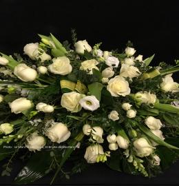 Coussin de cercueil Douceur. Jardin de fleurs blanches (roses, rosettes, freesias, tulipes, lysianthus et mufliers) déposées dans un lit de verdures. De 250$ à 270$.