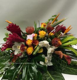 Coussin de cercueil Exotique. Fleurs dans les tons rouge, jaune et orangé (oiseaux du paradis, gingers, roses, callas, cymbidiums, leucospermums) et feuillages luxuriants. De 220$ à 270$.